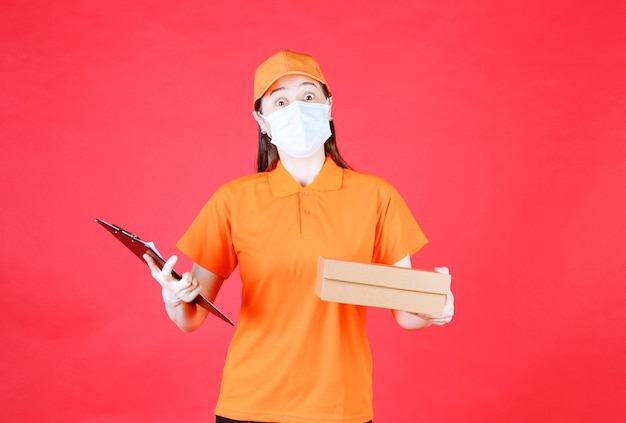 Female courier in orange color dresscode and mask holding a cardboard box and presenting the list for signature.