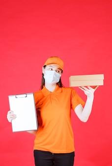 Corriere femminile in codice di abbigliamento e maschera di colore arancione che tiene una scatola di cartone e presenta l'elenco per la firma