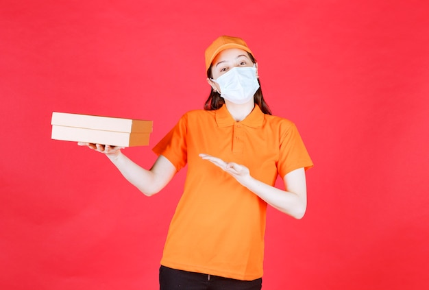 Female courier in orange color dresscode and mask holding a cardboard box and showing it.