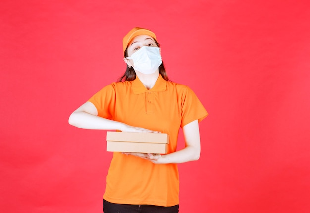 Female courier in orange color dresscode and mask holding a cardboard box .