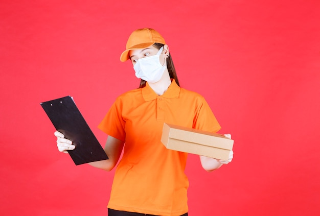 Female courier in orange color uniform and mask holding a cardboard box and reading the name and address.