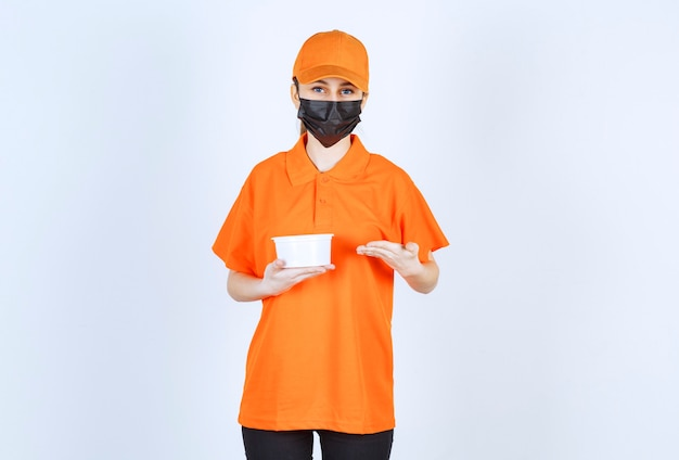 Female courier in orange uniform and black mask holding a plastic cup and pointing at something