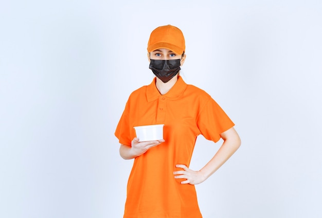 Female courier in orange uniform and black mask holding a plastic cup