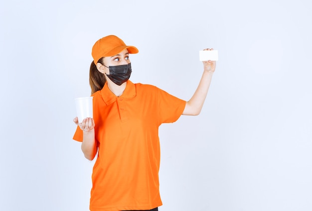 Female courier in orange uniform and black mask holding a plastic takeaway cup and presenting her business card