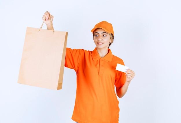 Corriere femminile in uniforme arancione che consegna una borsa della spesa di cartone e presenta il suo biglietto da visita