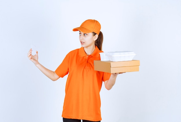 Female courier in orange uniform holding a cardboard box and a plastic takeaway box on it while presenting her business card.