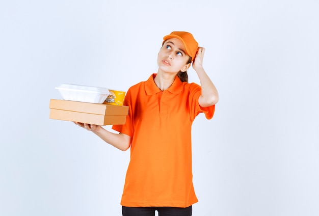 Female courier in orange uniform holding a cardboard box, a plastic takeaway box and a yellow noodles cup while looking confused and thoughtful.
