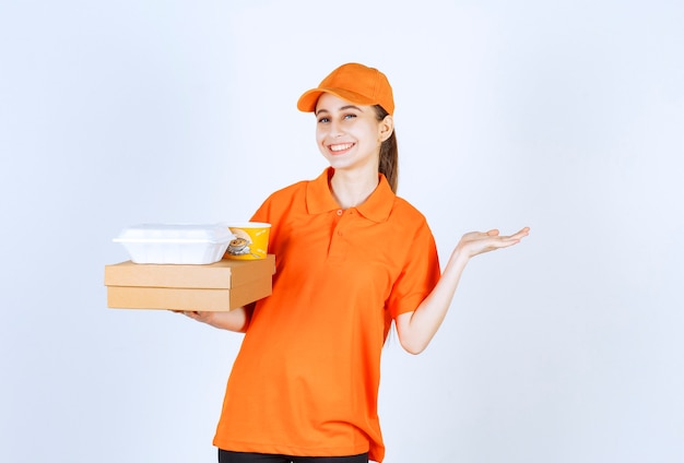 Female courier in orange uniform holding a cardboard box, a plastic takeaway box and a yellow noodles cup.