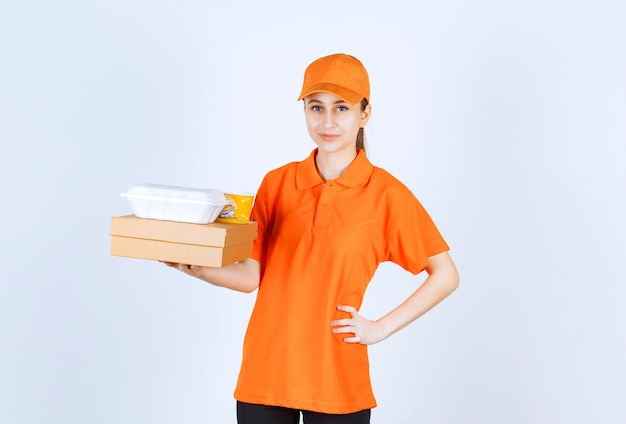 Female courier in orange uniform holding a cardboard box, a plastic takeaway box and a yellow noodles cup