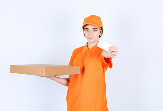 Corriere femminile in uniforme arancione che tiene una scatola di cartone e presenta il suo biglietto da visita
