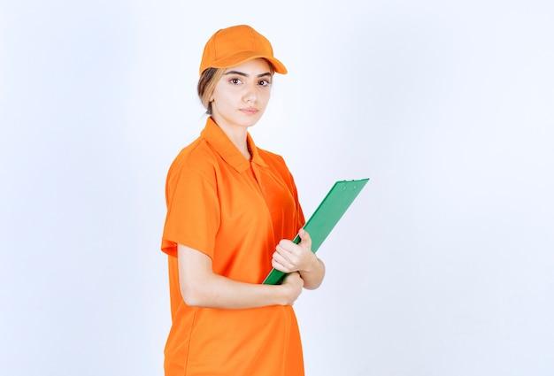 Female courier in orange uniform holding a green customer list