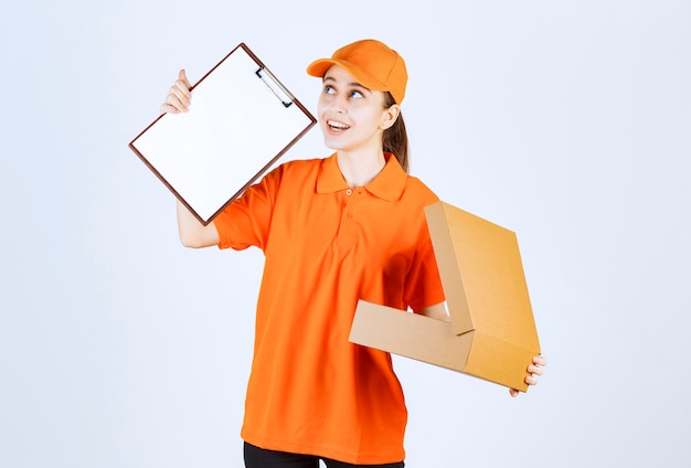Corriere femminile in uniforme arancione che tiene una scatola di cartone aperta e chiede una firma