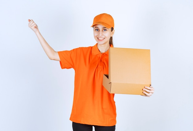 Female courier in orange uniform holding an open cardboard box and showing her fist.
