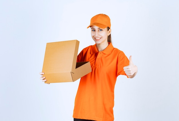 Female courier in orange uniform holding an open cardboard box and showing positive hand sign.
