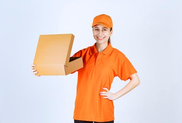 Corriere femminile in uniforme arancione che tiene una scatola di cartone aperta