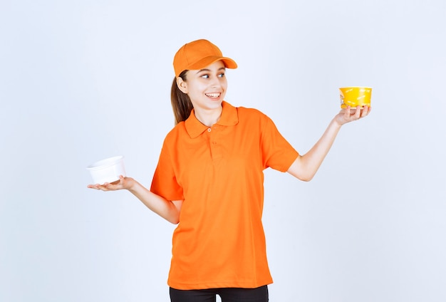 Corriere femminile in uniforme arancione che tiene una tazza di pasta di plastica e gialla in entrambe le mani