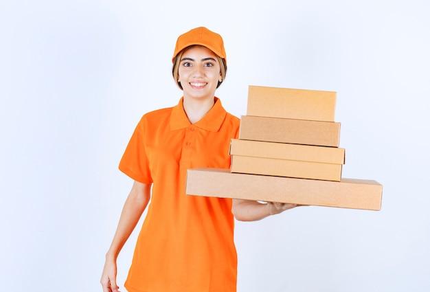 Corriere femminile in uniforme arancione che tiene una scorta di pacchi di cartone