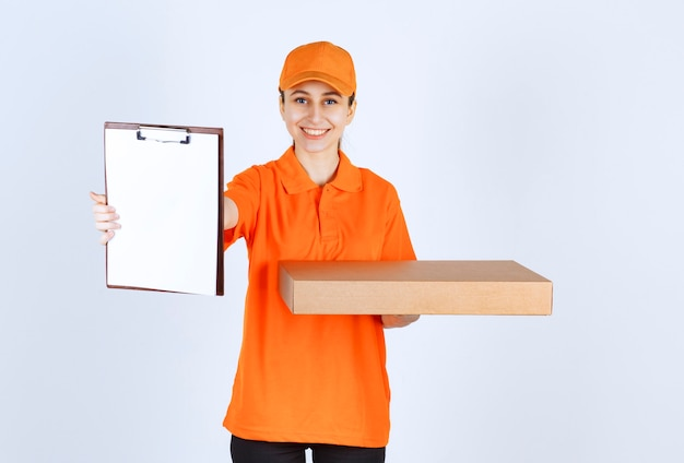 Female courier in orange uniform holding a takeaway pizza box and asking the signature of the customer.