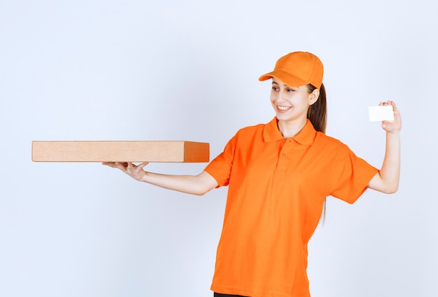 Female courier in orange uniform holding a takeaway pizza box and presenting her business card.