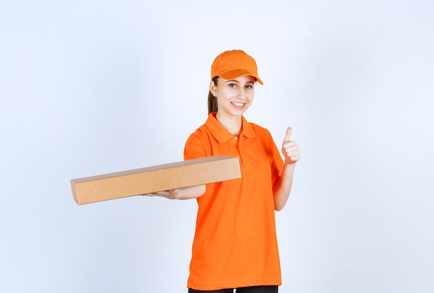 Female courier in orange uniform holding a takeaway pizza box and showing positive hand sign