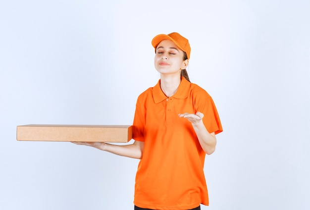Female courier in orange uniform holding a takeaway pizza box and smelling the product.