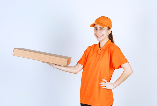 Female courier in orange uniform holding a takeaway pizza box