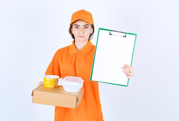 Female courier in orange uniform holding yellow and white takeaway boxes, cardboard parcel and a customer list for signature