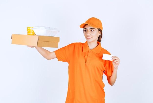 Corriere femminile in uniforme arancione con scatole da asporto gialle e bianche, pacco di cartone e presentando il suo biglietto da visita