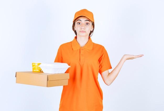 Corriere femminile in uniforme arancione con scatole da asporto gialle e bianche con un pacco di cartone e sembra confuso e pensieroso