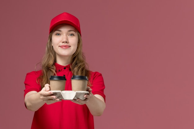 Female courier in red uniform holding brown delivery coffee cups and smiling on pink, uniform job worker service delivery