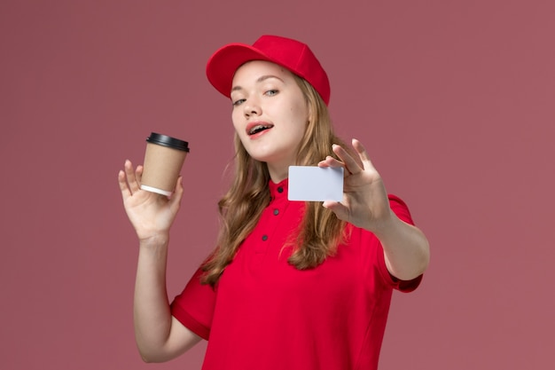 Female courier in red uniform holding coffee cup along with white card on light pink, job uniform worker service delivery