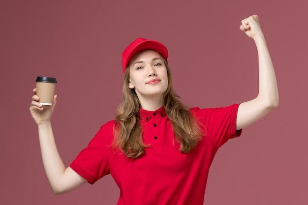 Corriere femminile in uniforme rossa che tiene la tazza di caffè e che flette sul rosa chiaro, consegna dei lavoratori di servizio dell'uniforme di lavoro