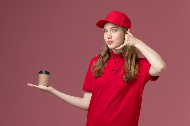 Female courier in red uniform holding coffee cup phone call posing on light-pink, job uniform service worker delivery