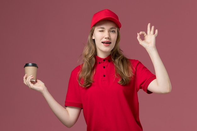 Female courier in red uniform holding coffee cup winking on pink, uniform service delivery job worker