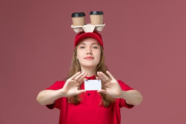 Corriere femminile in uniforme rossa che tiene tazze di caffè e carta con il sorriso sul rosa, consegna del servizio uniforme