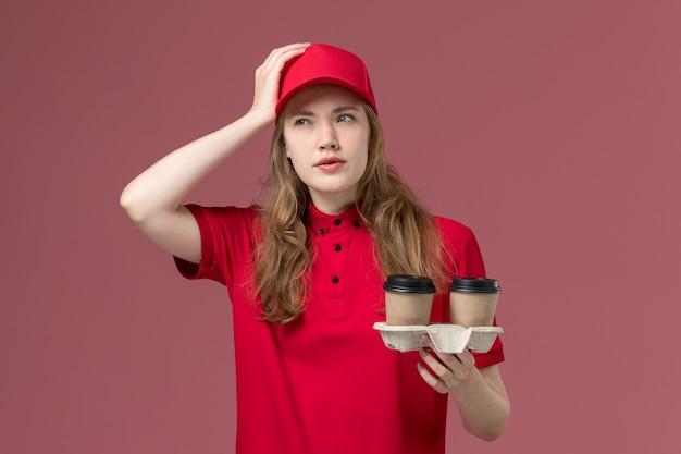 Corriere femminile in uniforme rossa che tiene tazze di caffè pensando in profondità sul lavoro di consegna del servizio rosa e uniforme