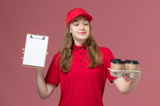 Corriere femminile in uniforme rossa che tiene tazze di caffè e blocco note con il sorriso sul lavoro di consegna del servizio rosa, uniforme