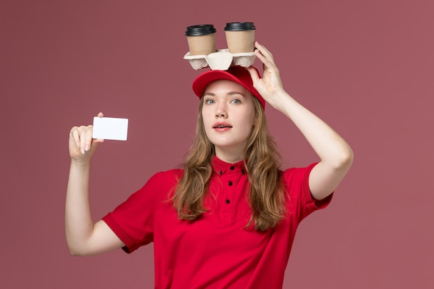Female courier in red uniform holding coffee cups with card on pink, uniform service delivering worker