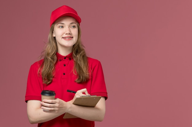 Female courier in red uniform holding coffee writing down notes on light pink, job uniform service worker delivery