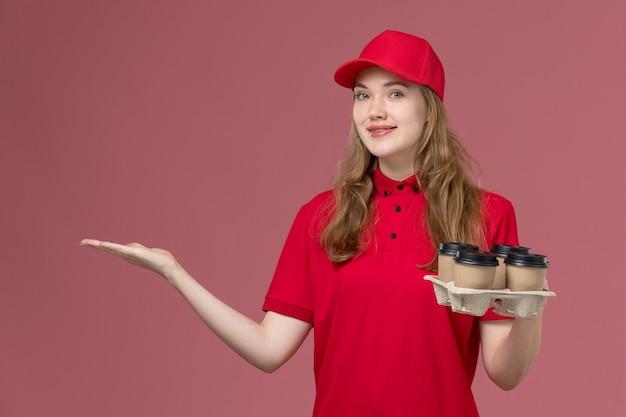 Corriere femminile in uniforme rossa che tiene le tazze di caffè marroni di consegna che posano sul rosa, lavoratore di lavoro di consegna di servizio uniforme