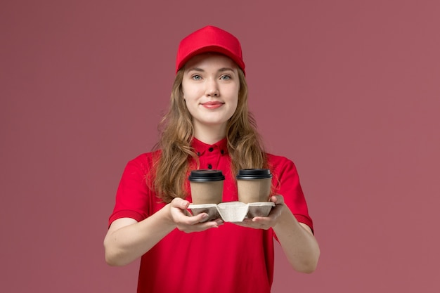 Female courier in red uniform holding delivery coffee cups smiling on light pink, job uniform service worker delivery