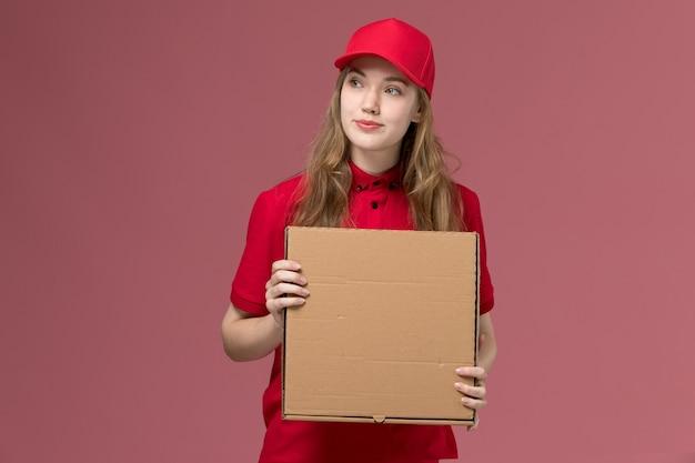 Corriere femminile in uniforme rossa che tiene la scatola di cibo di consegna sul lavoro di consegna del servizio uniforme del pavimento rosa