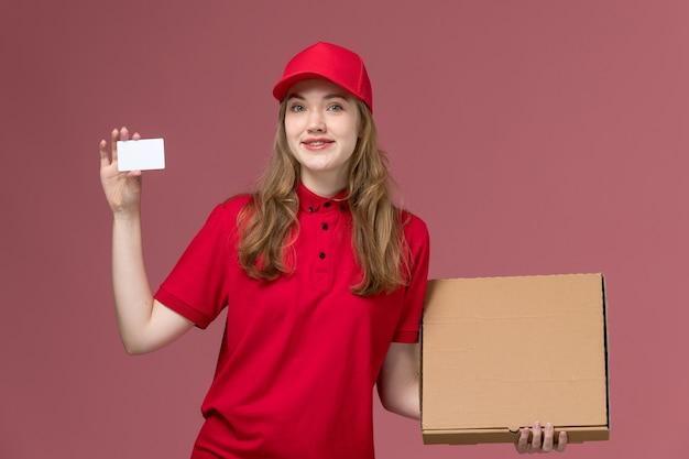Corriere femminile in uniforme rossa che tiene la consegna carta bianca scatola di cibo su rosa chiaro, ragazza di consegna del lavoratore di servizio di lavoro uniforme