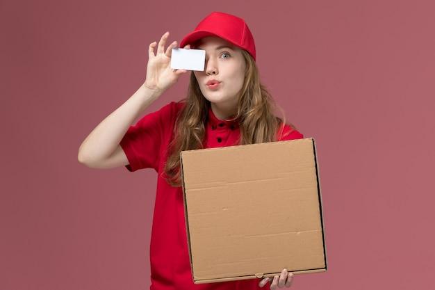 Corriere femminile in uniforme rossa che tiene scatola di cibo e carta su rosa, lavoratore di lavoro di consegna del servizio uniforme