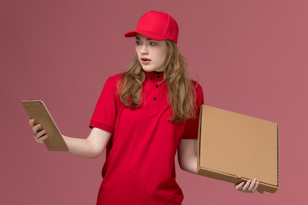 Female courier in red uniform holding food box notepad on pink, uniform service delivery worker job