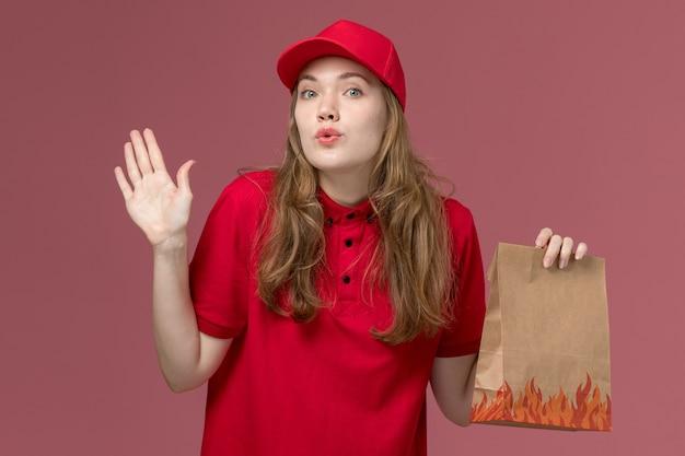 Corriere femminile in uniforme rossa che tiene il pacchetto di cibo e posa sulla consegna dei lavoratori di servizio di colore rosa chiaro, uniforme di lavoro