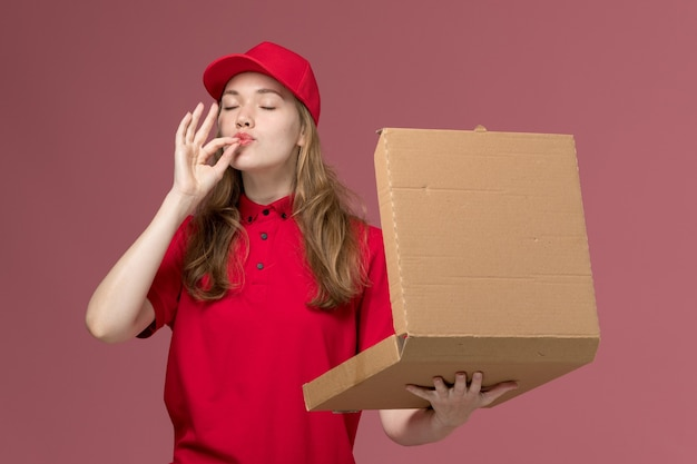 Female courier in red uniform holding opening food box on pink, uniform service delivering worker