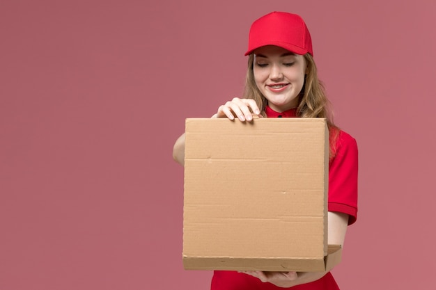 Female courier in red uniform holding opening food box with smile on pink, uniform service delivering worker