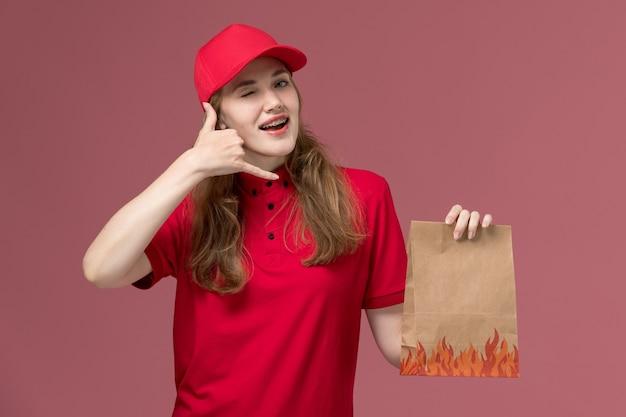 Corriere femminile in uniforme rossa che tiene il pacchetto di cibo di carta su rosa chiaro, consegna del lavoratore di servizio dell'uniforme di lavoro
