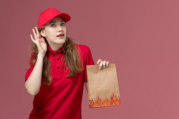Corriere femminile in uniforme rossa che tiene il pacchetto alimentare di carta cercando di ascoltare il rosa chiaro, consegna del servizio uniforme di lavoro